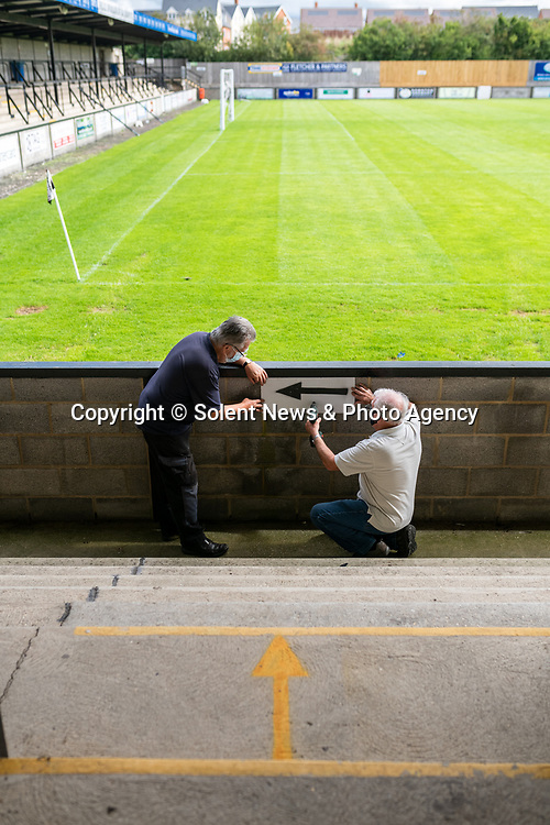 Pictured: Volunteer maintenance workers John Harper and Ray Neal drill an arrow to the wall during preparations ahead of crowds being welcomed back into sporting events at The Raymond McEnhill Stadium in Salisbury, Wilts.<br /> <br /> Inline with the governments easing of lockdown restrictions, Salisbury Football Club are preparaing to welcome back 30% of their fans as of this Monday, August 31st. <br /> <br /> Salisbury FC play in Southern League Premier Division South, or step 3 of the non-league football ladder. <br /> <br /> © Jordan Pettitt/Solent News & Photo Agency<br /> UK +44 (0) 2380 458800