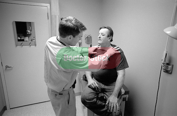 Middle age male patient seated on examination table describing symptoms to young male doctor in examination room