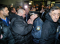 Pictured: Kostas Karapapas of Olympiakos speaks to a police officer outside the Toumba Stadium in Thessaloniki, Greece. Sunday 25 February 2018<br /> Re: Sunday's Greek Super League derby between PAOK Thessaloniki and Olympiakos was called off after Olympiakos' manager Oscar Garcia was struck in the face by an object believed to be a till machine paper roll, thrown by a spectator minutes before kick-off.<br /> Garcia left Toumba Stadium for a local hospital to seek treatment for a bloodied lip.<br /> The incident prompted the Olympiakos team to leave the pitch in protest before riots erupted outside the ground.<br /> Angry PAOK fans leaving the stadium then clashed with police who used tear gas to quell the violence.
