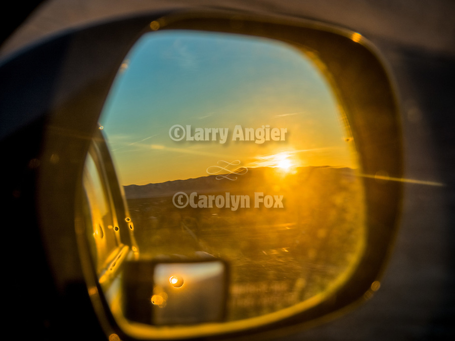 Rear-view mirror sunrise in the mirror at the Winnemucca Dunes along US-95 north of town in the late winter with snow.