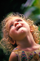Little girl looking up outside in nature