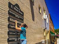 Worker installs sign for renamed pizza restaurant in Uptown Westerville.