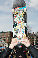 A man holds a skateboard with a depiction of US President Donald Trump as a zombie as people gather during the March For Our Lives protest and demonstration in Boston Common in Boston, Massachusetts, USA, on Sat., March 24, 2018. The march was held in response to recent school gun violence.