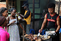 ANGOLA market on the road between Sumbe und Gabela, women buy grilled meat at street vendoor / ANGOLA Markt bei Gabela, Frauen kaufen Fleisch bei einem Strassengrill