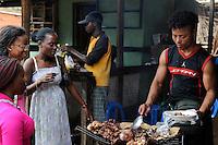 ANGOLA market on the road between Sumbe und Gabela, women buy grilled meat at street vendoor / ANGOLA Markt bei Gabela, Frauen kaufen Fleisch bei einem Strassengrill