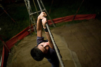 Daniel clings to the high-wire during a practice session at the Jhon Danyer Circus. Around a dozen small circuses wander the poorer neighbourhoods around the city of Medellin putting on performances in what can be a hand to mouth existence. Despite falling audience numbers, new health and safety regulations and other bureaucracy these small family businesses, many of whom have existed for generations, still scrape a living in a world where the people are more accustomed to being entertained by soap operas than by live entertainment.
