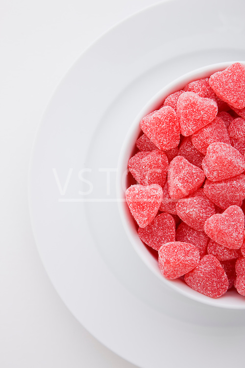 Red heart shape candies in bowl on white background