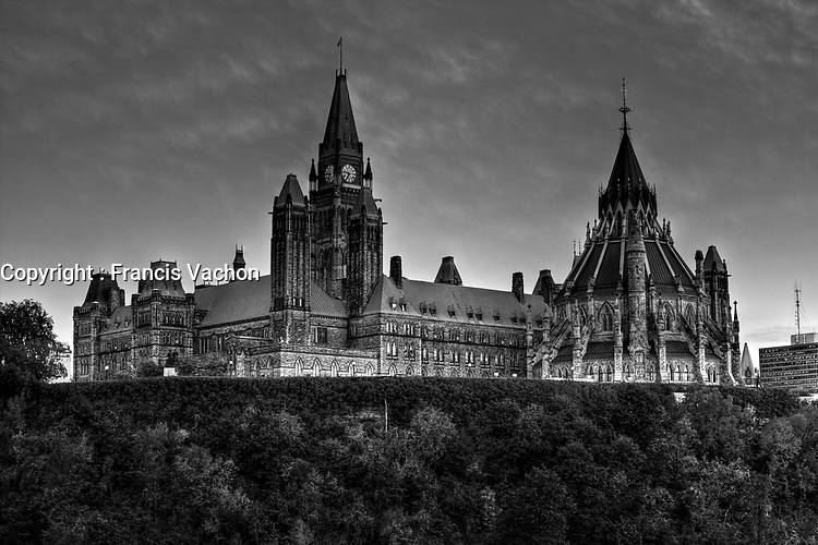 Sun set on the Parliament and the Library of Parliament in Ottawa Monday September 27, 2010. Parliament Hill (colloquially The Hill, in French: Colline du Parlement) is an area of Crown land on the southern banks of the Ottawa River in downtown with a Gothic revival suite of buildings, the parliament buildings, that serves as the home of the Parliament of Canada and contains a number of architectural elements of national symbolic importance.<br /> <br /> PHOTO :  Francis Vachon - Agence Quebec Presse