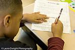 Education Elementary school Grade 2 boy working on English language arts worksheet horizontal