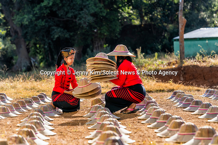 Hundreds of freshly-made bamboo hats are laid out to dry in rows on a baking hot day.  Workers placed about 300 handcrafted bamboo sun hats on a field next to the town of Pindaya in Myanmar.<br /> <br /> Here, workers weave the hats by hand before leaving them to dry in the sun.  SEE OUR COPY FOR DETAILS.<br /> <br /> Please byline: Jenny Kim/Solent News<br /> <br /> © Jenny Kim/Solent News & Photo Agency<br /> UK +44 (0) 2380 458800