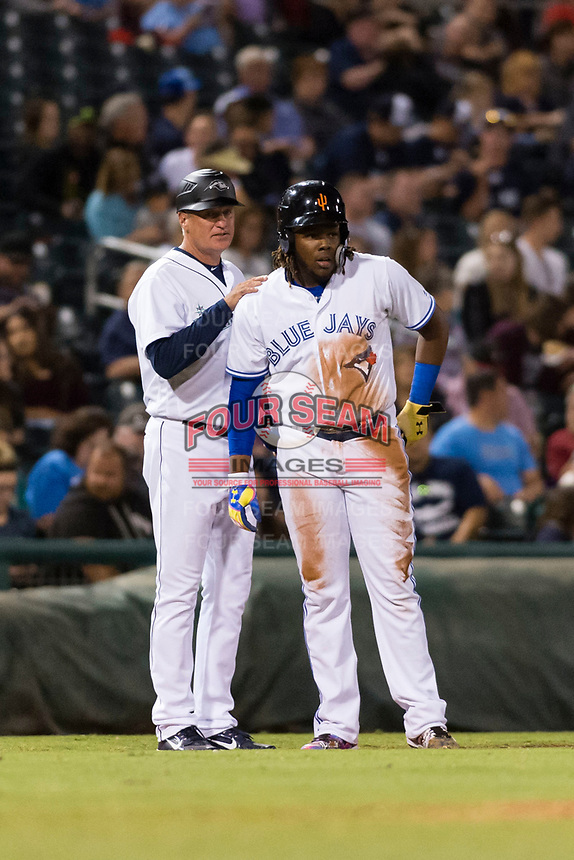 AFL West third baseman Vladimir Guerrero Jr. (27), of the Surprise Saguaros and Toronto Blue Jays organization, talks to manager Daren Brown (43) during the Arizona Fall League Fall Stars game at Surprise Stadium on November 3, 2018 in Surprise, Arizona. The AFL West defeated the AFL East 7-6 . (Zachary Lucy/Four Seam Images)