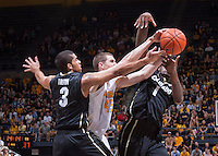 California's David Kravish and Colorado's Wesley Gordon and Xavier Talton fights for the ball during a game at Haas Pavilion in Berkeley, California on March 8th, 2014. California defeated Colorado 66 - 65