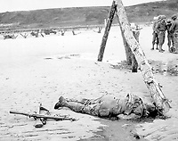 Crossed rifles in the sand are a comrade's tribute to this American soldier who sprang ashore from a landing barge and died at the barricades of Western Europe.  1944. (Coast Guard)<br /> Exact Date Shot Unknown<br /> NARA FILE #:  026-G-2397<br /> WAR & CONFLICT BOOK #:  1044