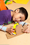 Education preschool 3-4 year olds boy playing by himself with wooden house block pieces talking to himself