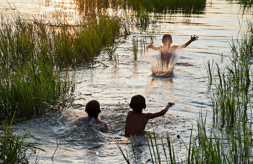 Late afternoon children playing in the flooded Rice fields during the Monsoon Season in the Rural area just outside Battambang, Cambodia