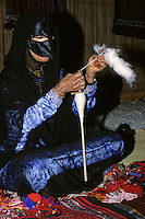 Muscat, Oman, Arabian Peninsula, Middle East - Bedouin woman spinning wool.  She wears a black abaya, and a face mask called a birqa. Cosmetic powder is applied under her eye.