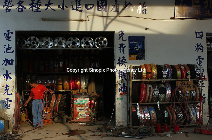 A worker at a garage passes a tyre stand, China.  .