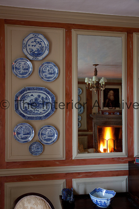 A reflection of General Tam can be seen in the mirror beside this plate display in the Blue Room
