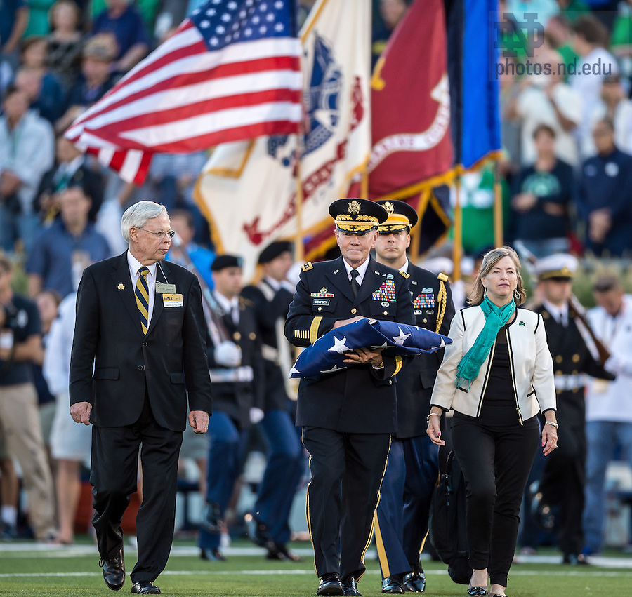 Sep. 6, 2014; Larry Dwyer, Assistant Director of Bands, walks with Chairman of the Joint Chiefs of Staff General Martin Dempsey as Gen. Dempsey presents the U.S. Flag before the start of the football game against Michigan. (Photo by Matt Cashore)