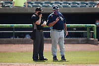 Myrtle Beach Pelicans manager Buddy Bailey (right) has a discussion with home plate umpire Ethan Gorsak during the game against the Lynchburg Hillcats at Bank of the James Stadium on May 23, 2021 in Lynchburg, Virginia. (Brian Westerholt/Four Seam Images)