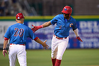 Clearwater Threshers manager Milver Reyes (28) congratulates Carlos De La Cruz (6) as he rounds third base after hitting a home run during a game against the Dunedin Blue Jays on May 18, 2021 at BayCare Ballpark in Clearwater, Florida.  (Mike Janes/Four Seam Images)