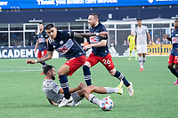 FOXBOROUGH, MA - JULY 25: Gustavo Bou #7 of New England Revolution breaks from a tackle by Henry Kessler #4 of New England Revolution during a game between CF Montreal and New England Revolution at Gillette Stadium on July 25, 2021 in Foxborough, Massachusetts.