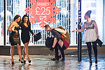 """© Joel Goodman - 07973 332324 . NO SYNDICATION PERMITTED . 20/12/2014 . Manchester , UK . A man carries a woman on his back , along Deansgate . """" Mad Friday """" revellers out in the rain and cold in Manchester . Mad Friday is typically the busiest day of the year for emergency services , taking place on the last Friday before Christmas when office Christmas parties and Christmas revellers enjoy a night out .  Photo credit : Joel Goodman"""