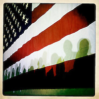 Shadows of supporters of Republican presidential candidate Mitt Romney appear on a flag at a rally Exeter, NH