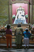 Cuba, Havana.  Worshippers Praying before a Shrine to Jesus and the Virgin Mary in La Merced Church.