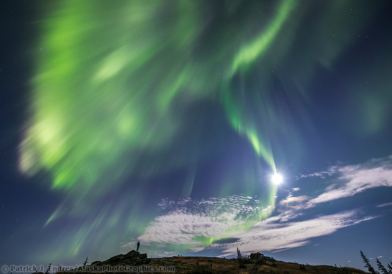 A man watches the aurora borealis, also called the northern lights, swirl over the foothills surrounding Fairbanks, Alaska.