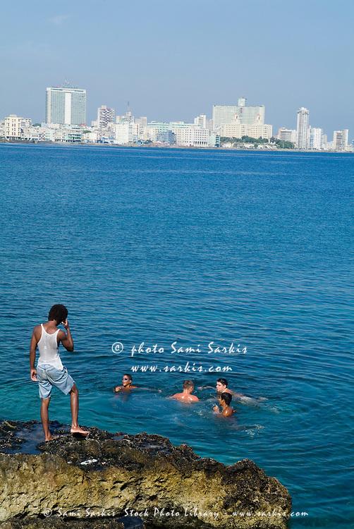 Cuban boys swimming in the Caribbean sea along the Malecón in Havana, Cuba.