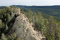 Photo story of Philmont Scout Ranch in Cimarron, New Mexico, taken during a Boy Scout Troop backpack trip in the summer of 2013. Photo is part of a comprehensive picture package which shows in-depth photography of a BSA Ventures crew on a trek. In this photo, a BSA Venture Crews  climb the front  surface of a natural rock, 50- feet off of the ground. The climbing was taking place at the  Cimarroncito Camp in the backcountry at Philmont Scout Ranch.   <br /> <br /> The  Photo by travel photograph: PatrickschneiderPhoto.com
