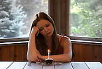 Young woman seated at a table looking at cupcake with single candle burning