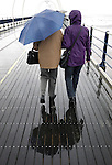 Easter Monday bad weather in Southport England. 9.4.12. Two people brave the wind and the rain for a walk along the pier.