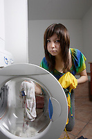 Montreal (Qc) CANADA, July 24, 2007 - Model Released photo- A young asian woman use high efficiency (HE) detergent to wash clothes in a front loader washing machine.<br /> <br /> Front-loading washing machines use:<br /> 40 to 60% less water<br /> 30 to 50% less energy<br /> 50 to 70% less detergent<br /> than top-loaders!