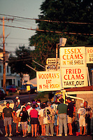 A line of tourists waits outside of Woodman's Eat in the Rough Restaurant; advertising signage for fried clams and clams in the shell. Essex, Massachusetts.