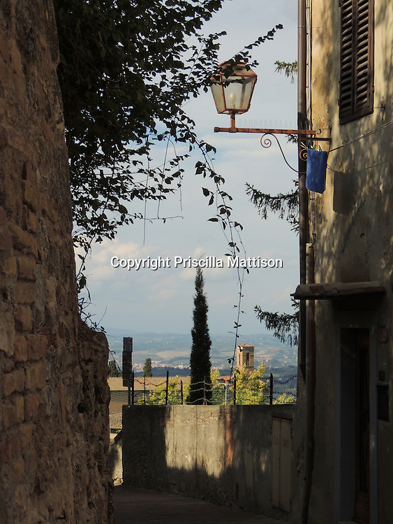 San Gimignano, Italy - October 4, 2012:  A view from a quiet lane to distant valleys.