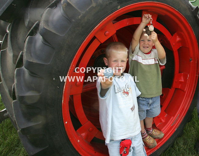 lunteren 130905 De buurkinderen van martin viets, wil jan en coen tonen het apparaatje wat ze bij zich moeten hebben om gededecteerd te worden door het kinderbeveiligingssysteem op landbouwmachines, dat martin ontwikkeld heeft.<br />foto frans ypma APA-foto