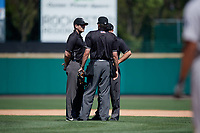 Umpires Richard Riley, John Bacon, and Mike Wiseman discuss a call during an International League game between the Scranton/Wilkes-Barre RailRiders and Rochester Red Wings on June 25, 2019 at Frontier Field in Rochester, New York.  Rochester defeated Scranton 10-9.  (Mike Janes/Four Seam Images)