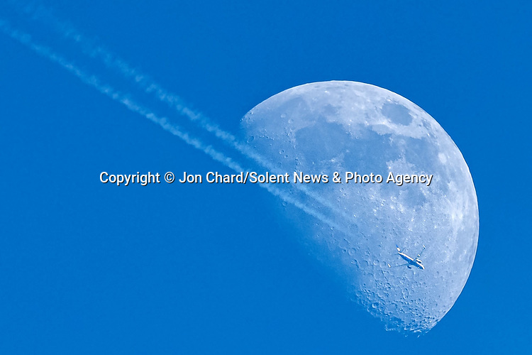Pictured: A airplane is dwarfed by the size of the moon as it leaves contrails across the bright blue sky. <br /> <br /> Photographer Jon Chard captured this great frame with his feet firmly rooted to the ground whilst shooting peregrines in New Milton, Hants.<br /> <br /> Mr Chard was using a 700mm lens to capture this shot of a Ryanair Boeing 737-800. As it made its way across the sky. <br /> <br /> Please byline: Jon Chard/Solent News<br /> <br /> © Jon Chard/Solent News & Photo Agency<br /> UK +44 (0) 2380 458800