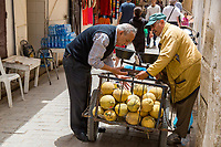 Fes, Morocco.  A Seller of Melons with a Customer in the Medina.