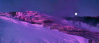 937000033 panoramic view of the full moon setting as dawn alpenglow turns snow covered minerva springs and the surrounding snow a soft magenta as steam rises from the boiling hot springs water on a cold winter morning in yellowstone national park in wyoming