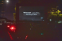 """A title card reading """"We the People want a future free from gun violence"""" is seen on a screen as people gathered to watch the 2020 Democratic National Convention at a """"Ridin' with Biden"""" Drive-In Theater viewing event at Suffolk Downs in Boston, Massachusetts, on Wed., Aug. 19, 2020."""