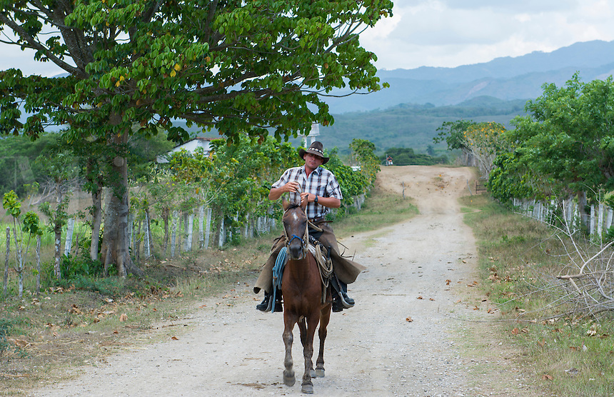 Trinidad Cuba cowboy on horse in country riding pon trail in ranch with hat and chaps and cowboy clothes