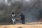 Palestinian protesters use a larag slingshot to hrul stones during clashes with Israeli security forces at tents protest at the Israel-Gaza border where Palestinians demand the right to return to their homeland, in Khan Younis in the southern Gaza Strip on April 20, 2018. Photo by Ashraf Amra