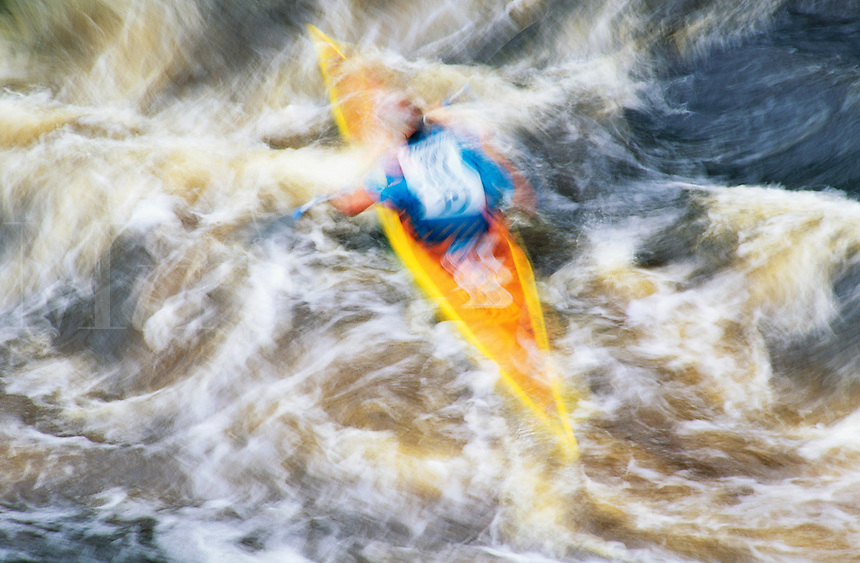 Blurred motion image of a kayaker in rapids.