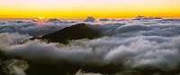 View of a golden sunrise high above the clouds from the HALEAKALA NATIONAL PARK on Maui in Hawaii
