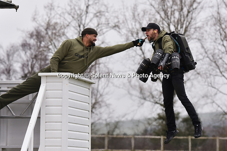 """Pictured: Member of dance troupe Diversity, Ashley Banjo feeds owner and test pilot of Gravity Technologies Richard Browning a Grenade Energy bar at Goodwood Aerodrome. <br /> <br /> Dance troupe Diversity, known for flying through the air in their stage performances, today took to the air outside - with jetpacks strapped to their hands.  Diversity members including founder Ashley Banjo, Jordan Banjo and Perri Kiely, donned Gravity Industries' cutting edge human-flight suit and took to the skies powered by Grenade Energy.<br /> <br /> Ashley, 32, said: """"Ahead of the day we were certain Pel would smash it, he's annoyingly very good at pretty much everything he puts his energy into.  SEE OUR COPY FOR DETAILS.<br /> <br /> © Solent News & Photo Agency<br /> UK +44 (0) 2380 458800"""