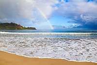 Surfers under a rainbow over Hanalei Bay, as waves roll towards Hanalei Beach, Kaua'i.
