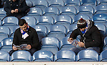 Rangers fans reading their programmes at half-time